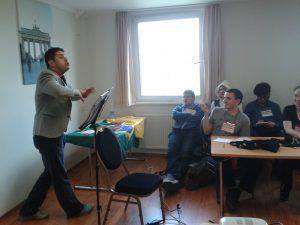 Jimmy Mello conducts a Portuguese lesson. With music stand, minus baton.
