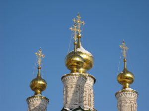 Golden Russian onion domes atop an ancient church
