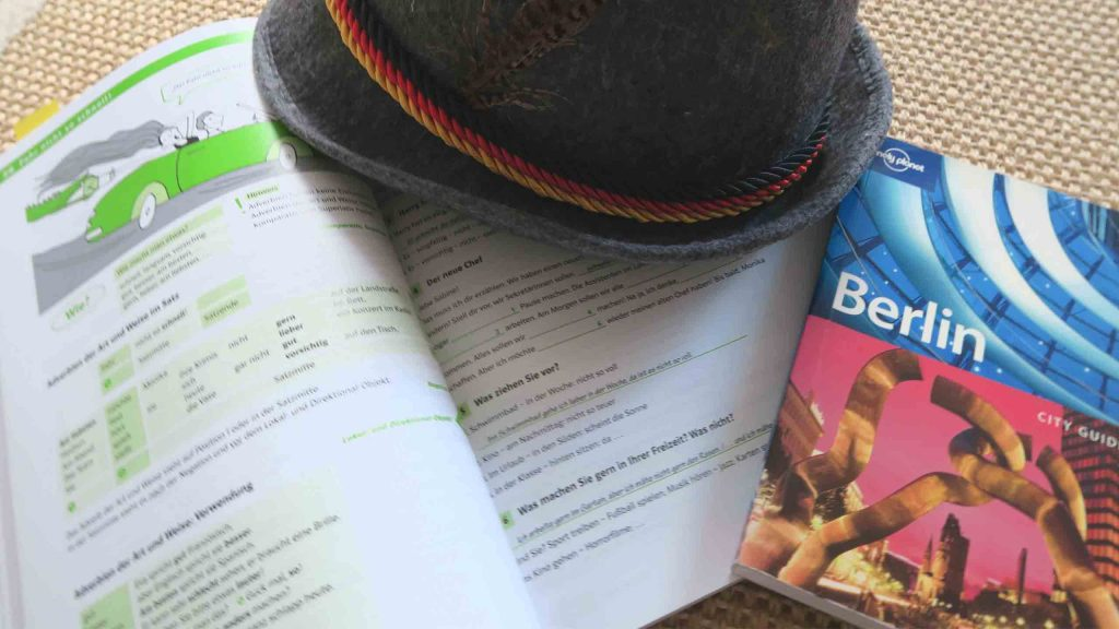 German textbook, travel guide and a German hat